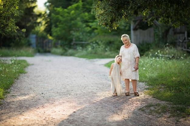 祖母と孫娘は白い古着を着て公園を歩き回る