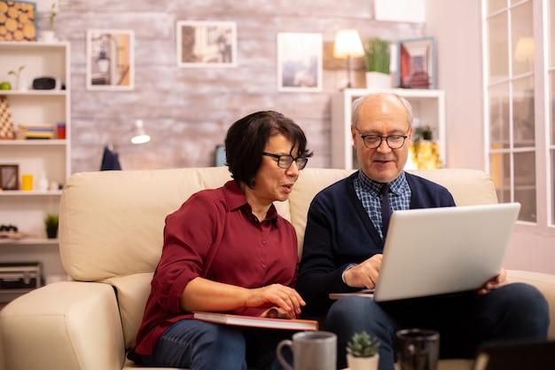 Бабушка и дедушка разговаривают с внуками за ноутбуком. старые люди, использующие современные технологии