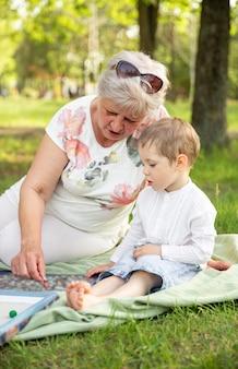 春の公園で一緒にボードゲームをしている祖母と孫