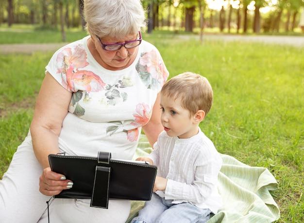 祖母と孫がタブレットを使用しています。家族で余暇を楽しむ