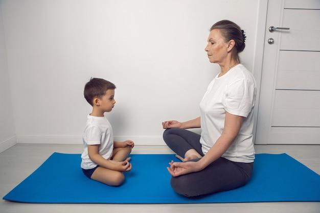 Бабушка и ее внук сидят на коврике для йоги в белой квартире дома и медитируют в позе лотоса.