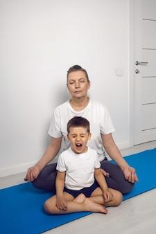 Бабушка и ее внук сидят на коврике для йоги в белой квартире дома и медитируют.