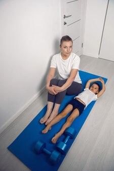 Бабушка и ее внук сидят на коврике для йоги в белой квартире.
