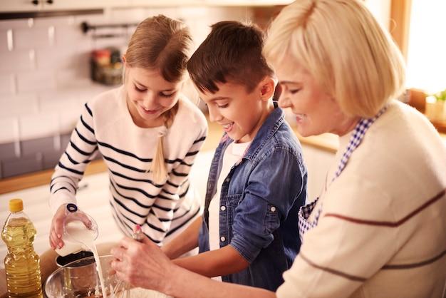 祖母と子供たちが何か特別なものを準備している