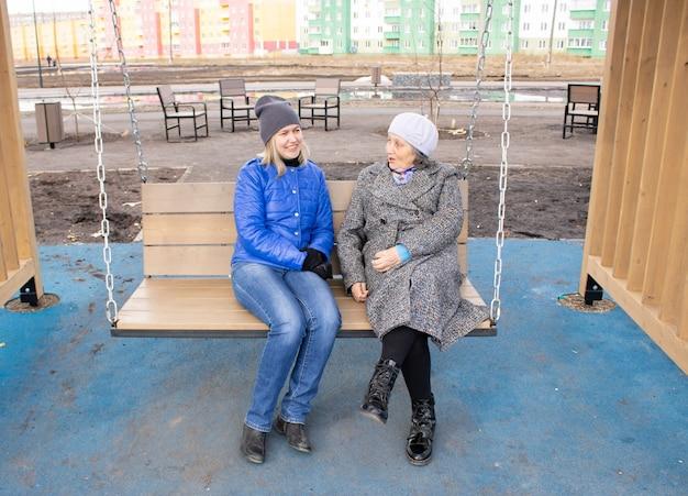추운 날씨에 따뜻한 옷을 입고 그네에 앉아 웃고 있는 할머니와 여성