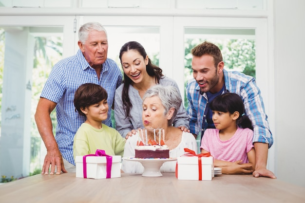 Grandmother blowing birthday candles with family