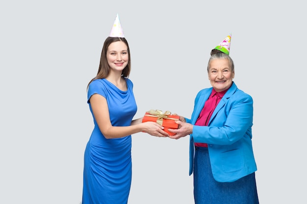 Grandmother in blue suit and hat holding red gift box and giving to her lovely granddaughter on her birthday. family happiness life event celebration. indoor studio shot, isolated on gray background