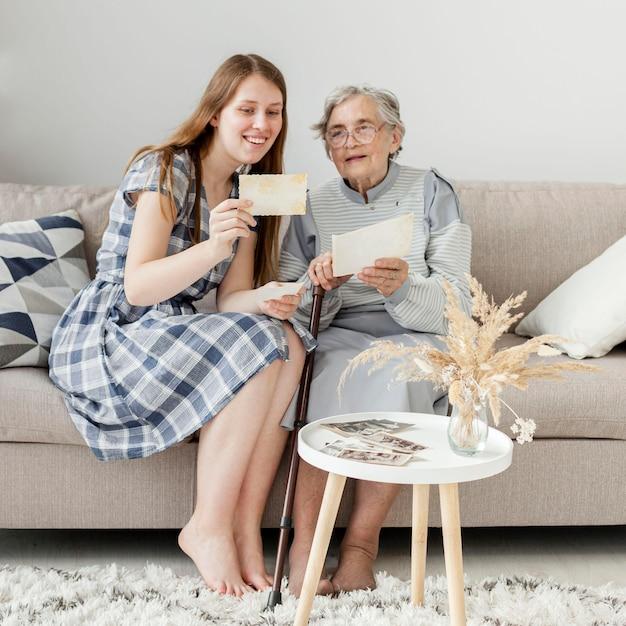 Бабушка проверяет старые фотографии с внучкой