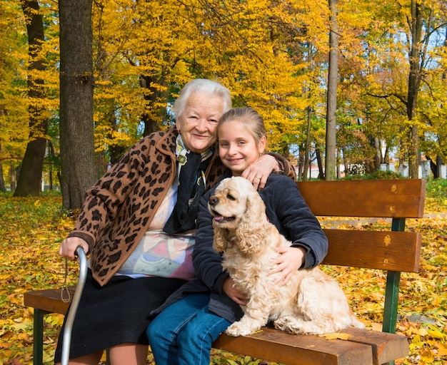 Grandmother and child sitting on the bench in the autumn park