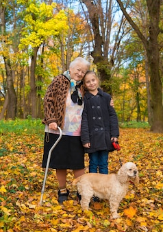 Grandmother and child walking in the autumn park