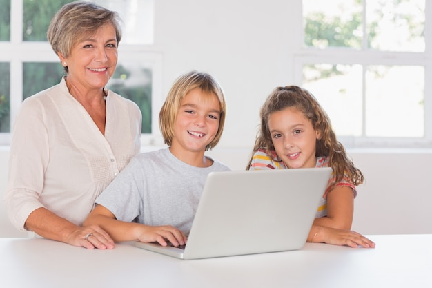 Grandmother and children looking at the camera together with laptop in front