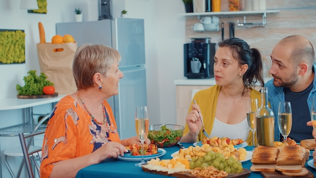 Grandmother cliking and discussing during the dinner. multi generation, four people, two couples happy talking and eating during a gourmet meal, enjoying time at home, in the kitchen sitting by the ta