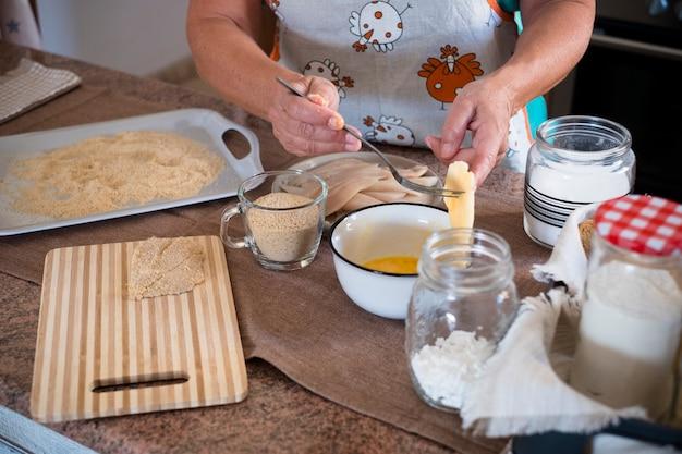 家で魚を料理する祖母-キッチンで屋内-引退した先輩-写真の腕と手