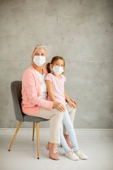 Grandmother and cute little granddaughter wearing a respiratory masks