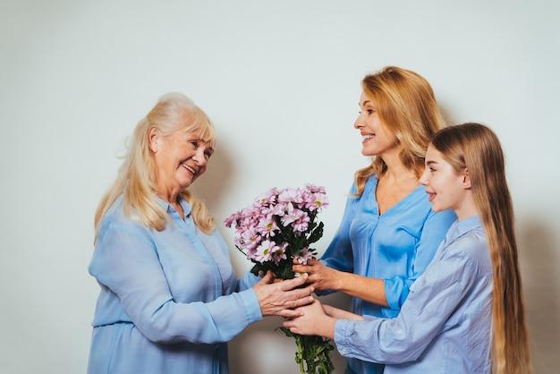 祖母、娘、孫が家で一緒にたくさんの花をあげる
