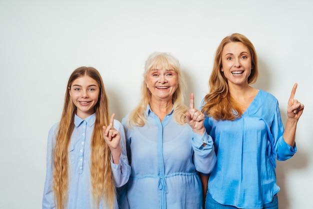 Бабушка, дочь и внук вместе дома, указывая вверх