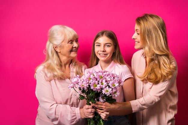 祖母、娘、孫が一緒にたくさんの花を持っています