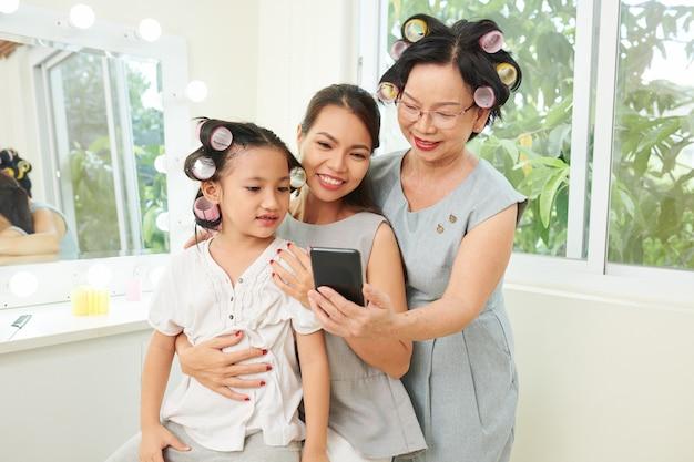 ヘアカーラーを適用するときにスマートフォンでチュートリアルを見ている祖母、娘、孫娘