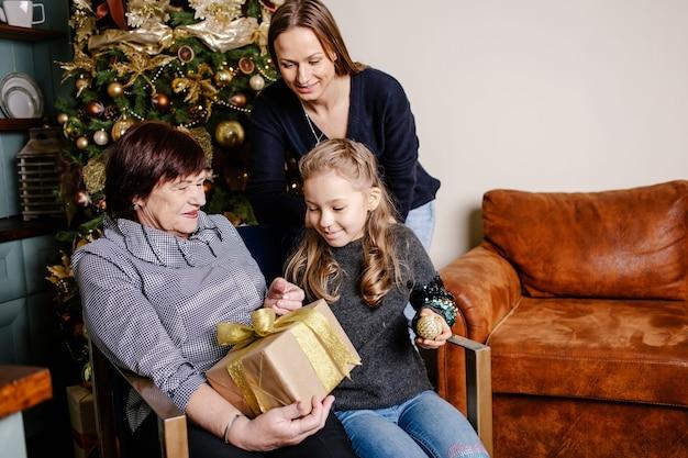 Бабушка обнимает и дарит внучке рождественский подарок.