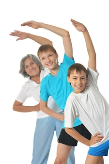 Бабушка тренируется с двумя детьми мальчиков, изолированные на белом фоне