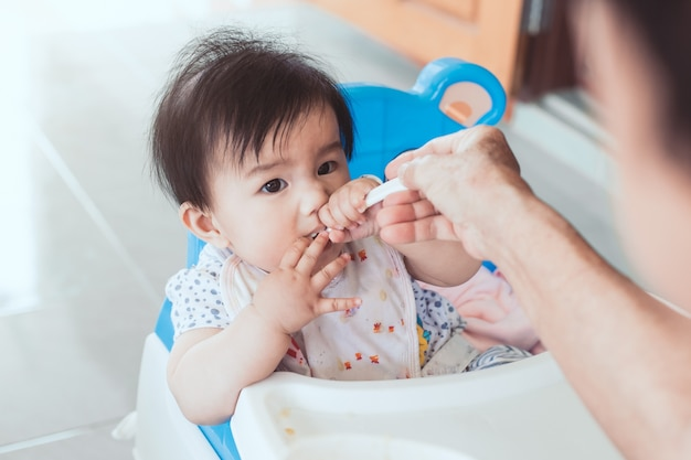Grandmother feeding cute asian baby girl with a spoon at home.