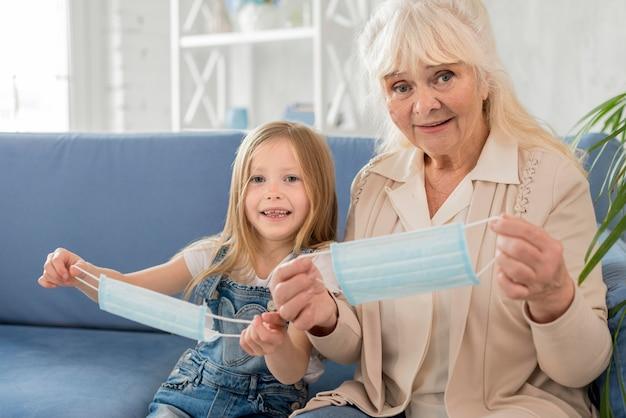 Grandmother and girl putting mask
