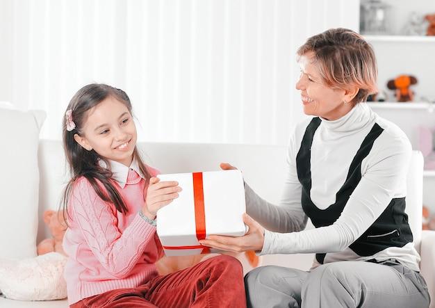 Бабушка дарит внучке коробку с подарком.