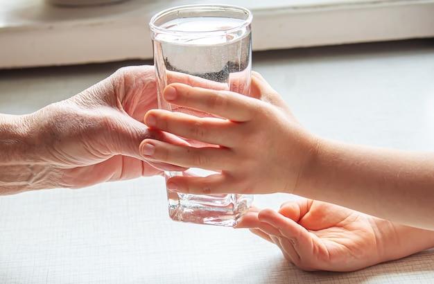 祖母が子供にきれいな水を一杯与える。セレクティブフォーカス。自然。