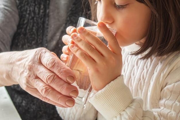 祖母が子供にきれいな水を一杯与える。セレクティブfocus.people