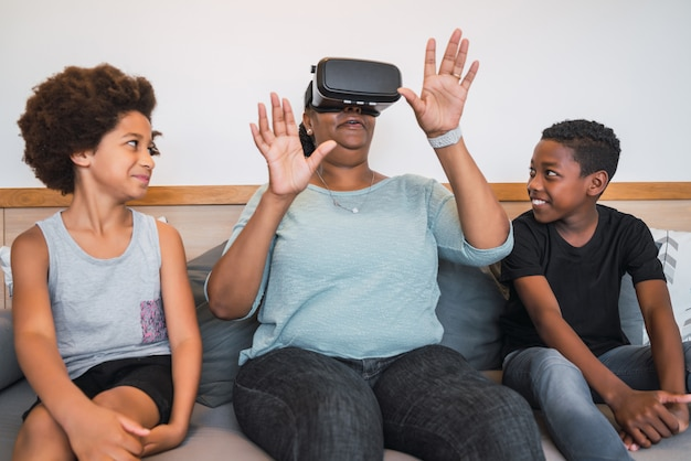 Grandmother and grandchildren playing together with vr glasses.