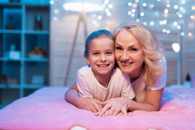 Grandmother and granddaughter are hugging at night at home.
