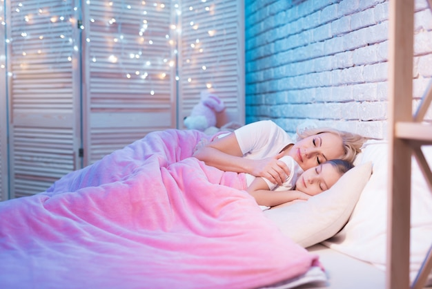 Grandmother and granddaughter are lying in bed at night.