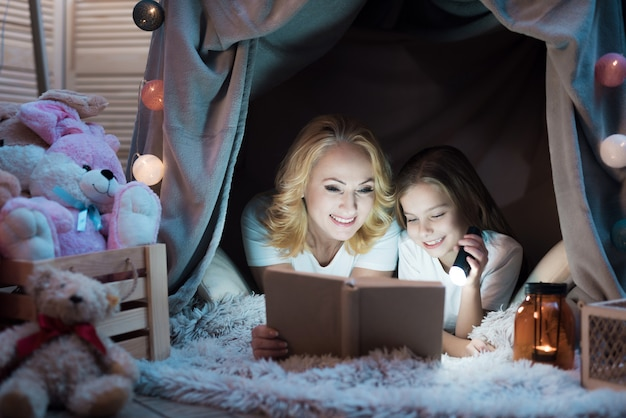 Grandmother and granddaughter are reading book at night.