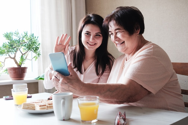 Grandmother and granddaughter communicate together with relatives via video communication