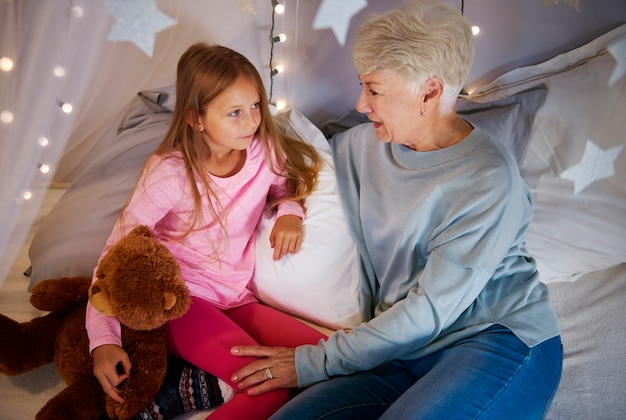 Grandmother and granddaughter interacting in bedroom