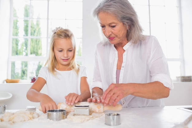 Grandmother and granddaughter making biscuits together