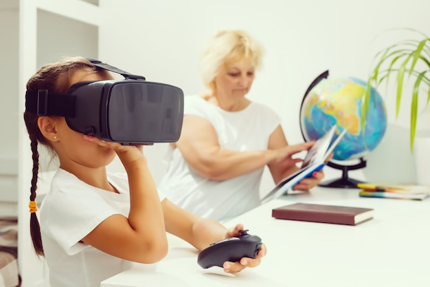Grandmother and granddaughter playing with virtual reality goggles
