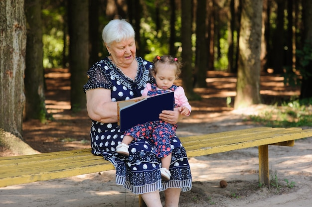 Grandmother and granddaughter reading the book in the park
