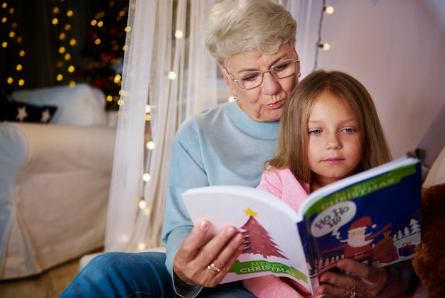 Grandmother and granddaughter reading storybook in bed