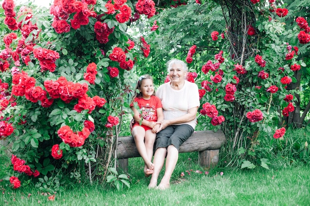Grandmother and granddaughter sit barefoot on a log bench in the garden