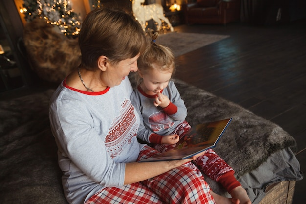 Grandmother and granddaughter sit on bed in pajamas and reading book.