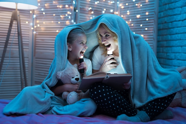 Grandmother and granddaughter sitting under blanket at night