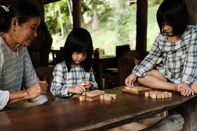 Grandmother and granddaughter smile happily family relationships play wooden block