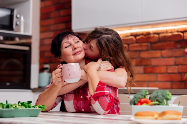 Grandmother and granddaughter spend leisure time together in the kitchen