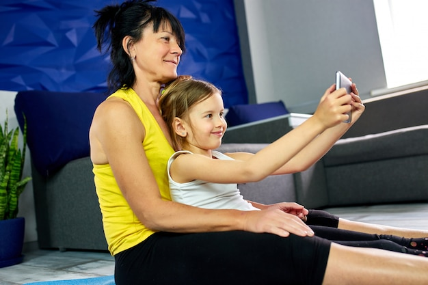 Grandmother and granddaughter taking selfie together at home.