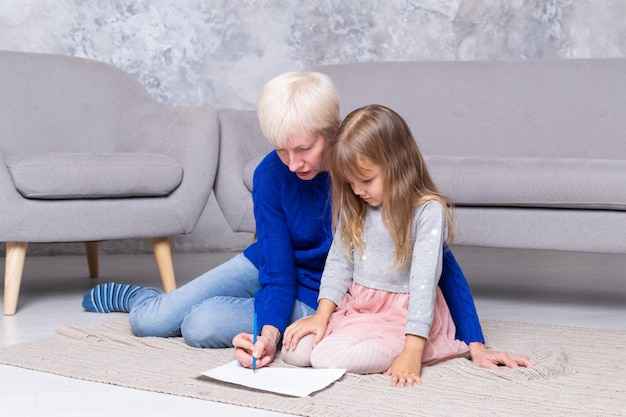 Grandmother and granddaughter together paint at living room floor. adult woman helps the kid draw a picture