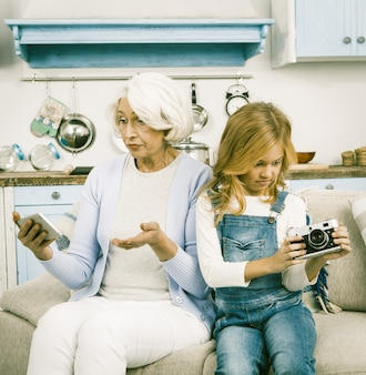 Grandmother and granddaughter trying to use camera