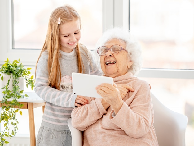 Grandmother and granddaughter using a tablet