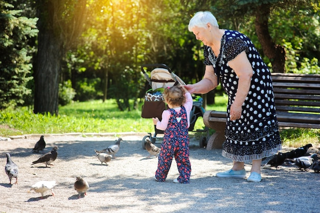Grandmother and granddaughter walk in the park