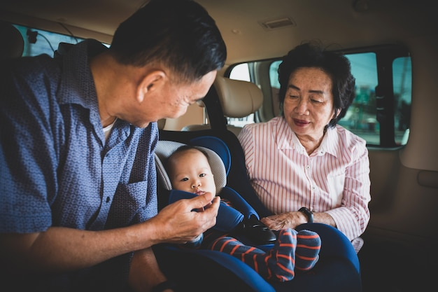 Grandmother and grandfather takes care about her little granddaughter in a car, helps her and cheers up
